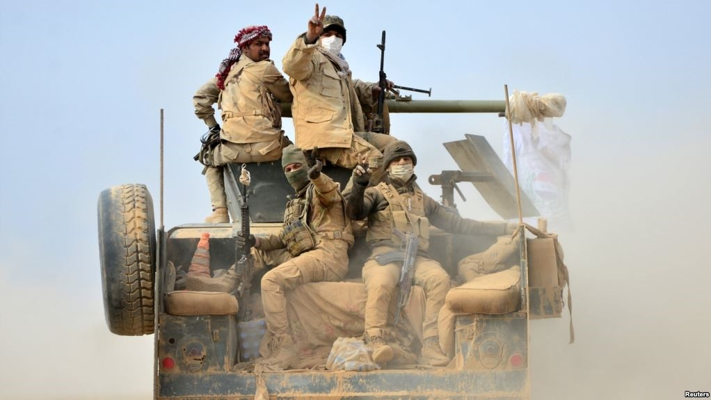 Hashd al-Shaabi forces ride on a military vehicle heading toward the airport of Tal Afar during a battle with Daesh militants in Tal Afar, Nov. 16, 2016.