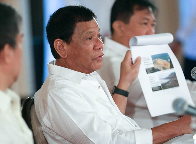 Filipino President Rodrigo Duterte displaying photos of environmental damage on mining sites, during a press conference inside Malacanang presidential palace in Manila, Philippines, on March 13, 2017. (EPA Photo)