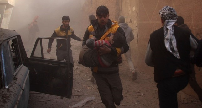 Members of the Syrian a volunteer civil defense group the White helmets, evacuate wounded people following airstrikes in the Eastern Ghouta region on the outskirts of the capital Damascus, Jan. 8.
