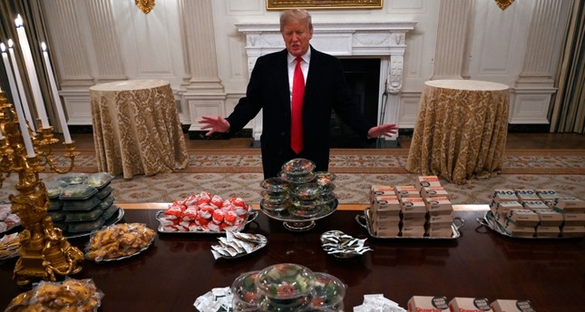 President Donald Trump talks to the media about the table full of fast food in the State Dining Room of the White House in Washington, Monday, Jan. 14, 2019 (AP Photo)