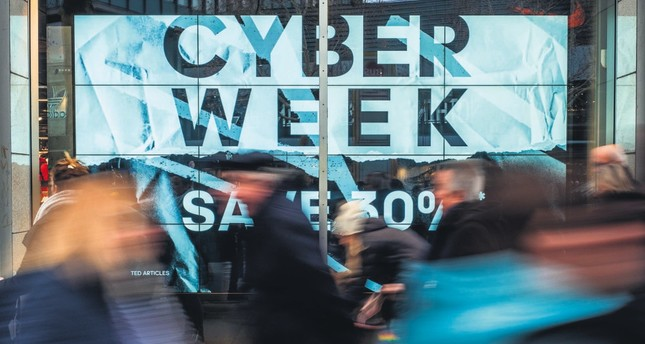 Shoppers walk past a store advertising a so-called Cyber Week sale, in Berlin, Nov.23.