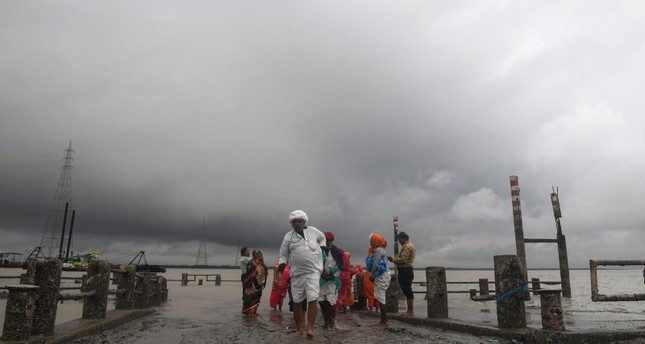 Hindu pilgrims walk back from the dock after a ferry service to Sagar Island was suspended due to the approaching Cyclone Bulbul in Kakdwip in West Bengal state on Nov. 9, 2019 AFP Photo