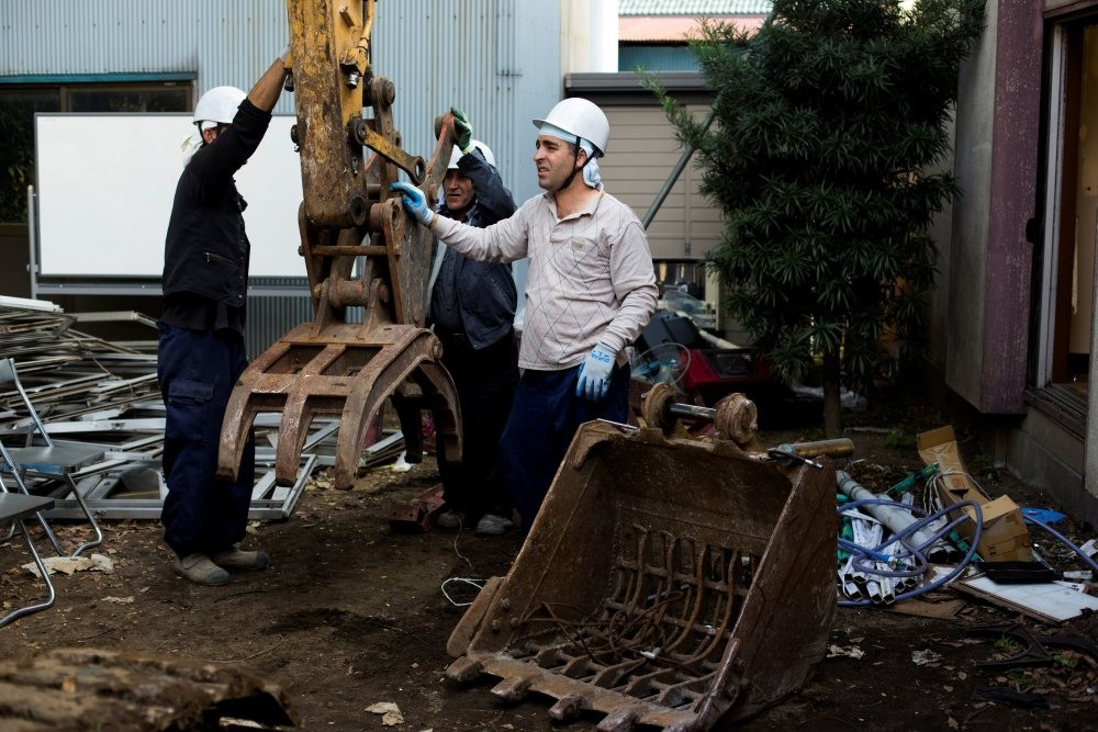 Foreign workers work at a demolition site in Chiba east of Tokyo.
