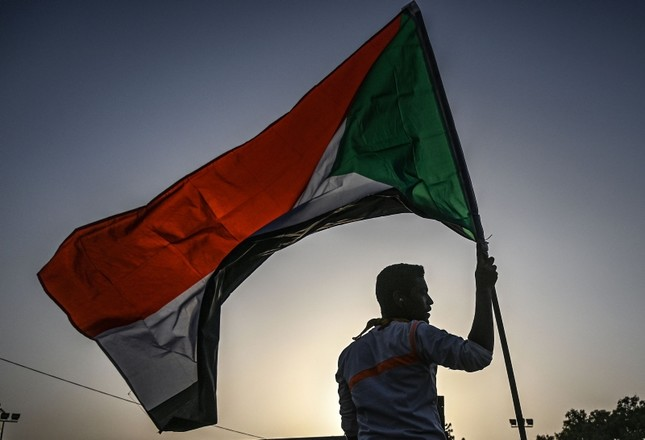 A Sudanese protester waves the national flag during a rally outside the army complex in Sudan's capital Khartoum on April 18, 2019. (AFP Photo)