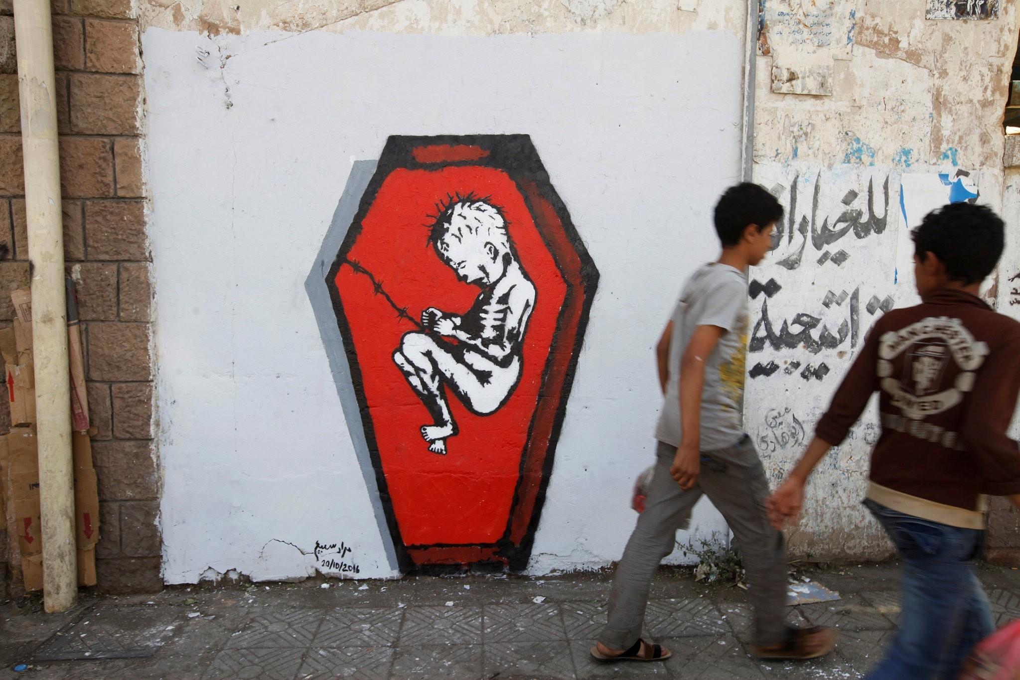 Boys walk pass a graffiti of artist Murad Subai depicting a child suffering from malnutrition in a coffin along a street in Sanaa, Yemen, October 20, 2016. (REUTERS Photo)