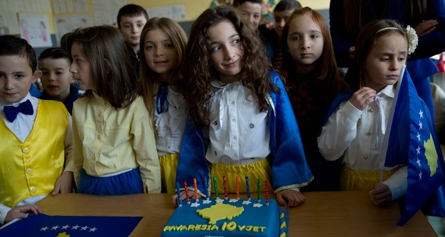 Pavaresia Sopi, 10, center, stands next to her birthday cake during an independence celebration ceremony at a school in the village of Sllovi near the town of Lipjan, Kosovo on Friday Feb. 16, 2018 (AP Photo)