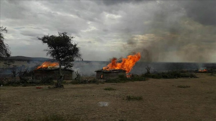 A plume of smoke billowing from a burned hut in Loliondo Tanzania.
