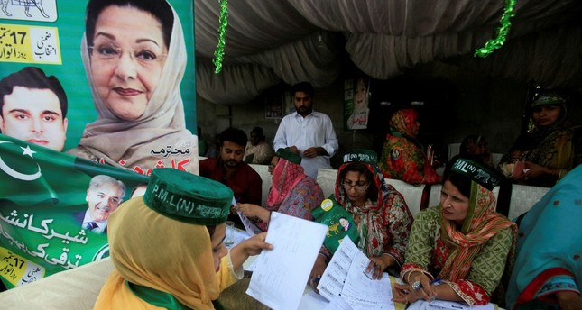 Workers of the PMLN political party guide voters outside a polling station in Lahore, Pakistan, Sept. 17.