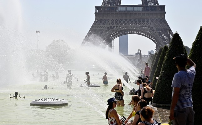 People cool off and sunbathe at the Trocadero Fountains in Paris, on July 25, 2019 as a new heatwave hits the French capital. (AA Photo)