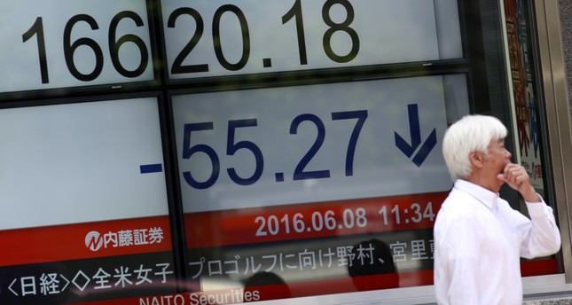 A man stands near an electronic stock board showing Japan's Nikkei 225 index at a securities firm in Tokyo.