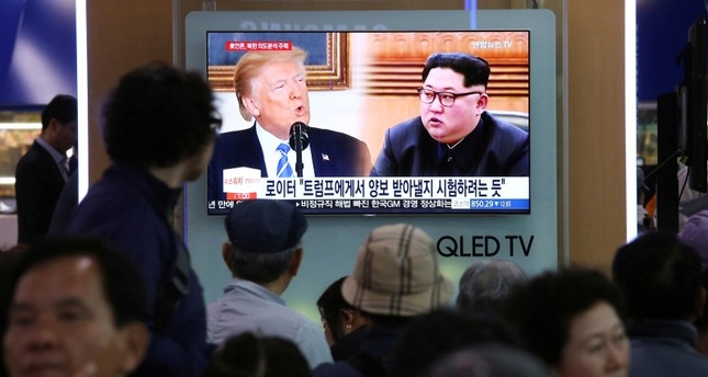People watch a TV screen showing file footage of U.S. President Donald Trump, left, and North Korean leader Kim Jong Un during a news program at the Seoul Railway Station in Seoul, South Korea, Wednesday, May 16, 2018. (AP Photo)