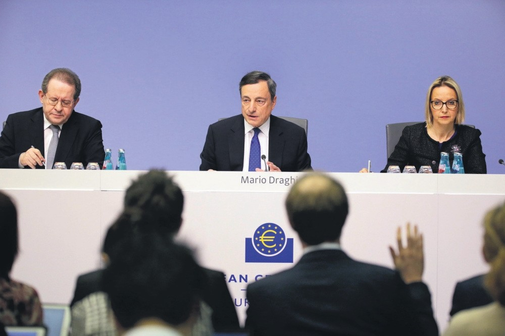 President of the European Central Bank (ECB), Mario Draghi (C), is flanked by Vitor Constancio (L), Vice-President of the European Central Bank, as he speaks to media during a press conference.