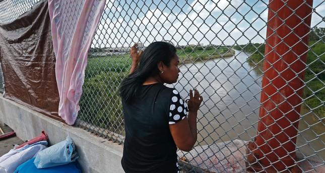 An immigrant seeking asylum looks out across the Rio Grande River while waiting in the middle of the bridge to get into the U.S. from Matamoros, Mexico.