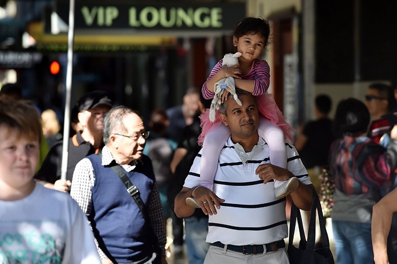 People walk on a street in Sydney on April 20, 2017 (AFP Photo)