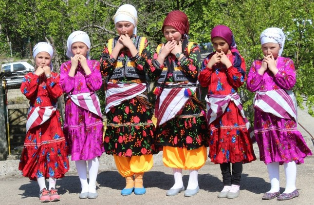 A group of children in traditional costumes gesture in kuşdili, Giresun's whistled language, in this undated photo.