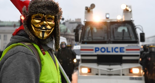 A masked protestor stands in front of a police vehicle in Paris on January 5, 2019, during a rally by yellow vest Gilets Jaunes anti-government protestors. (AFP Photo)