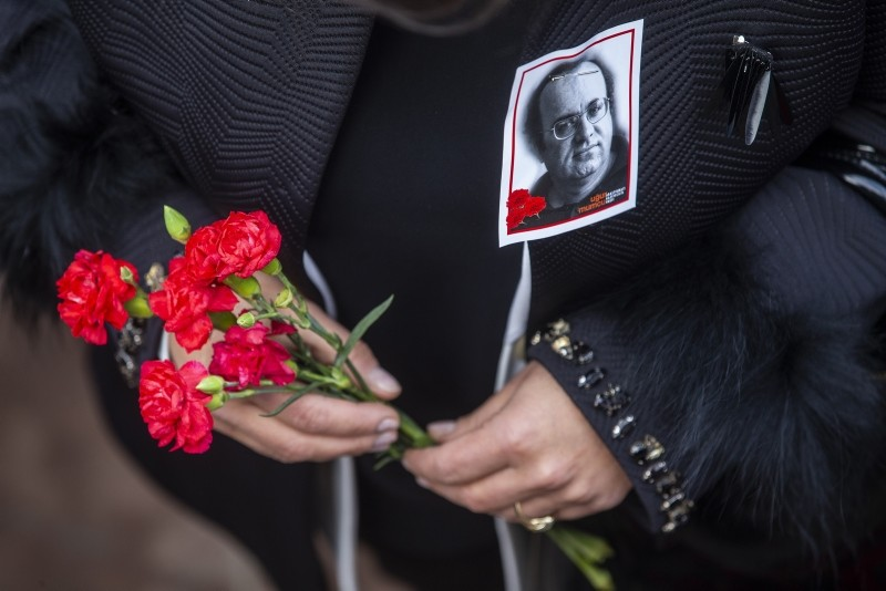 A woman with a photo of journalist Uu011fur Mumcu pinned to her coat holds flowers during a commemorative ceremony on the 26th anniversary of his assasination, in Ankara, Turkey, Thursday, Jan. 24, 2018. (AA Photo)