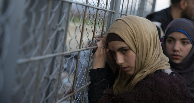 A young Syrian woman leans on the metal fence separating them from Macedonia at the Greek border station of Idomeni, Feb. 28. (AP Photo)