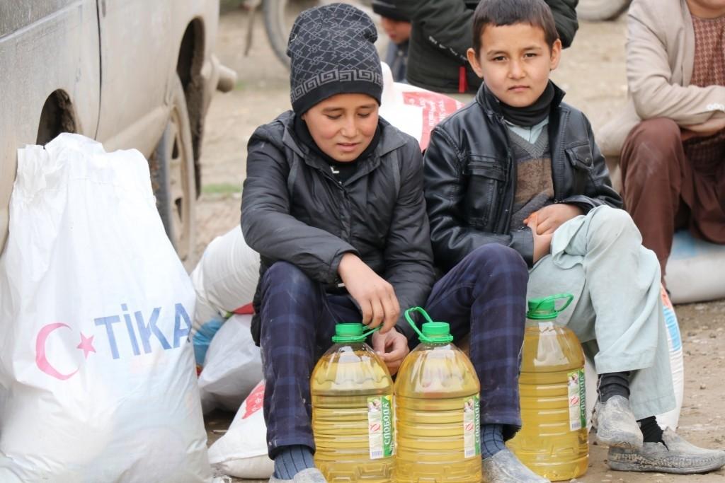 Two children sit beside packages of food aid distributed by Tu0130KA in Kunduz, Feb. 11, 2019.