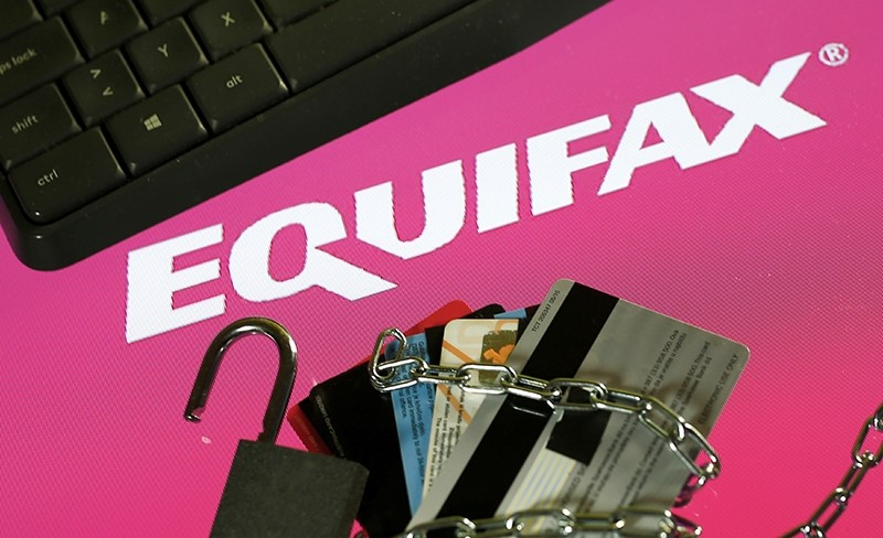 Credit cards, a chain and an open padlock is seen in front of displayed Equifax logo in this illustration taken September 8, 2017. (REUTERS Photo)