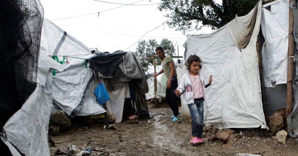 A girl makes her way next to tents at a makeshift camp for refugees and migrants, following a rainfall on the island of Lesbos, Greece, Oct. 8, 2019. (Reuters Photo)