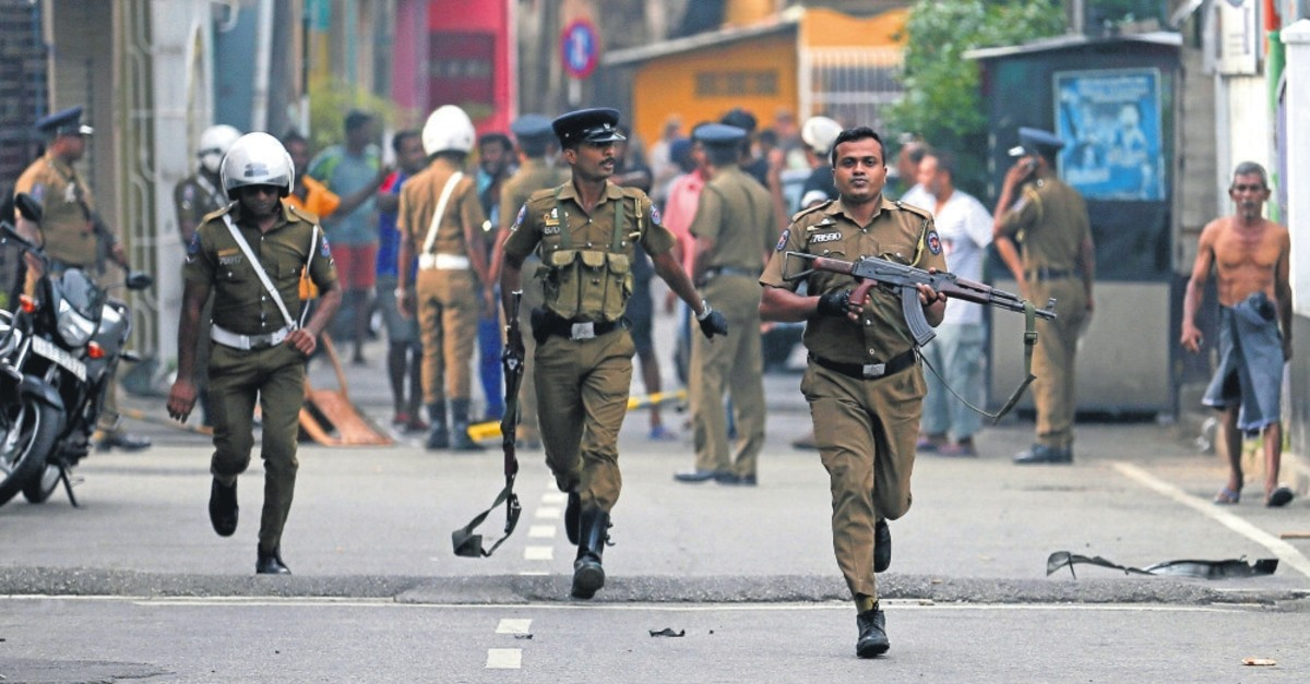 Sri Lankan police clear the area while Special Task Force Bomb Squad officers inspect the site of a van explosion, Colombo, April 22, 2019.