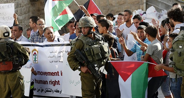Israeli soldiers stand guard as Palestinians hold thier national flag during a protest against Israel's increasing raids in the West Bank city of Hebron, Aug. 24, 2016.