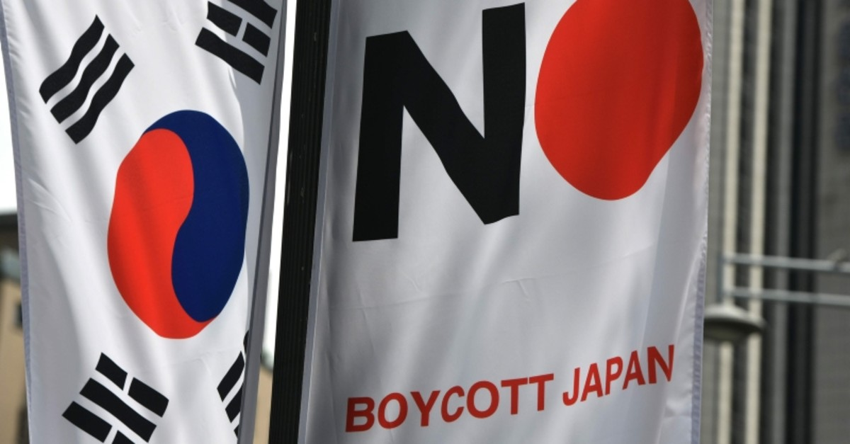 A South Korean flag (L) and a banner (R) that reads ,Boycott Japan, hangs along a street in Seoul's Jung-gu district on August 6, 2019. (AFP Photo)
