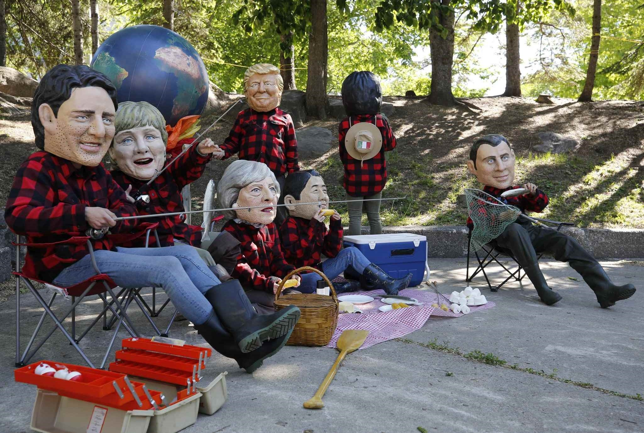 Protesters wearing giant papier mache heads depicting G7 leaders pose during a demonstration, Quebec, Canada, June 9.