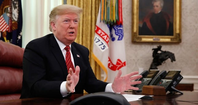 President Donald Trump greets members of the five branches of the military by video conference on Christmas Day, Tuesday, Dec. 25, 2018, in the Oval Office of the White House. (AP Photo)