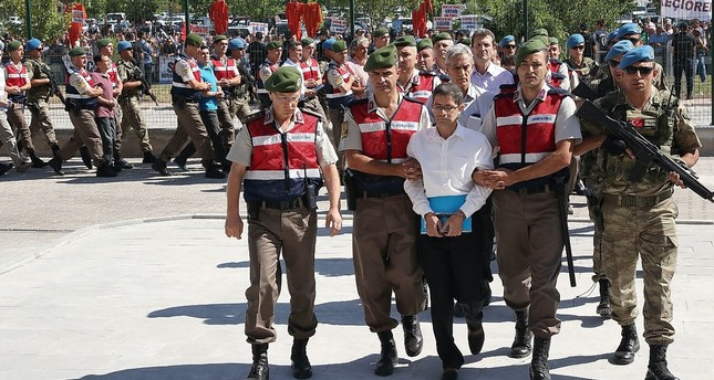 Gendarme troops escort Kemal Batmaz and other defendants to the courtroom in Ankara's Sincan district in a 2017 hearing.