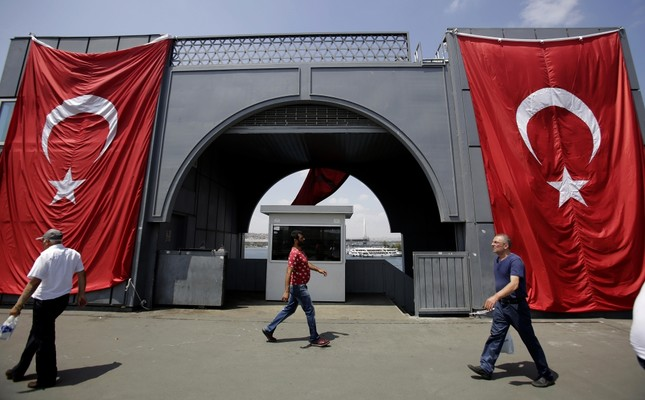 Men walking Galata Bridge where Turkish flag is displayed to protest the Gülenists' failed coup attempt, Istanbul, Aug. 2.
