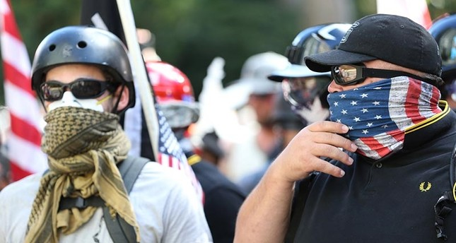 People demonstrate in a march by Patriot Prayer in Portland, Ore., on Saturday, June 30, 2018. Police dispersed clashing protesters as problems occurred when two opposing protest groups — Patriot Prayer and antifa — took to the streets. (AP Photo)