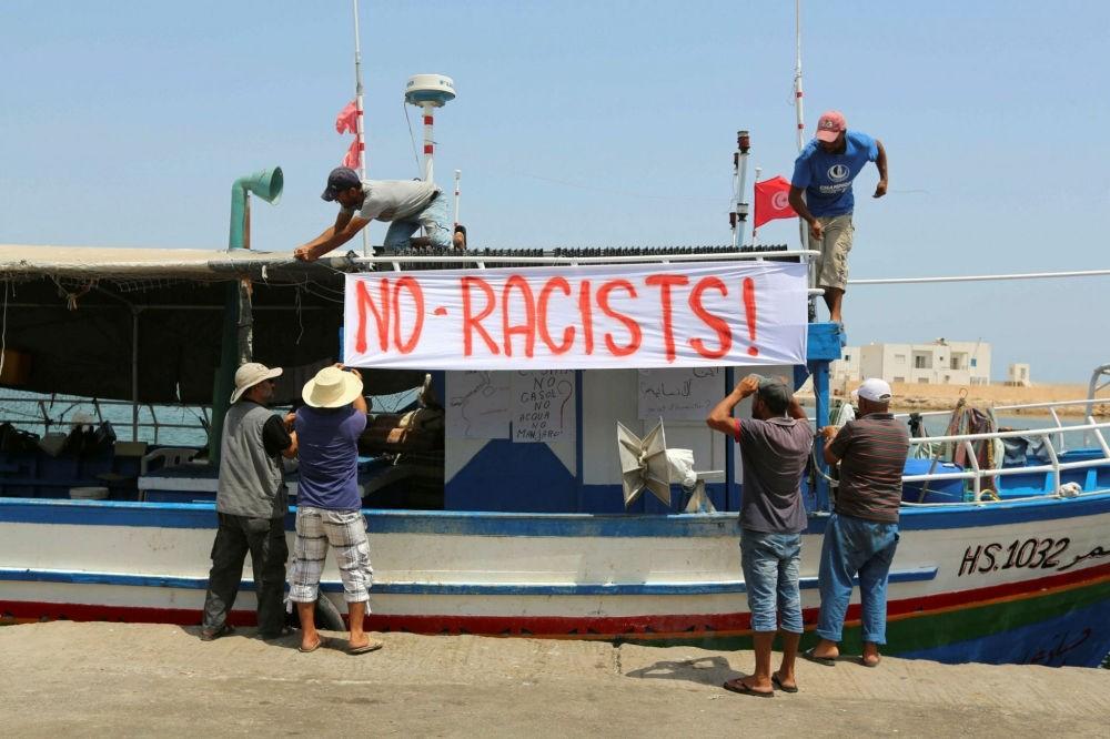Tunisian fishermen hang banners in the port of Zarzis in southeastern Tunisia, Aug. 6.