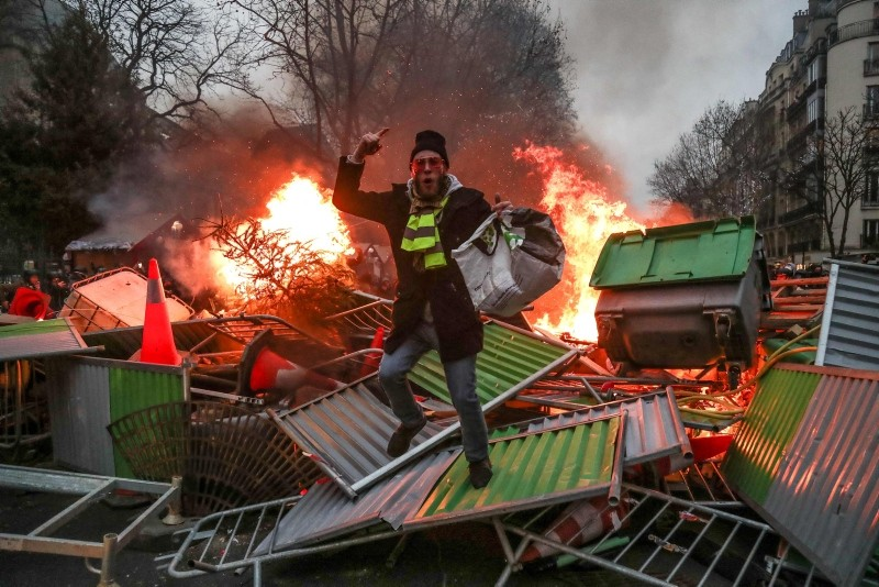 A yellow vest ,Gilets Jaunes, anti-government protestor stands on a burning barricade in Paris on January 5, 2019 during clashes with security personnel. (AFP Photo)