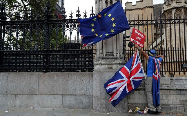 A demonstrator holds a sign that reads Brexit: Is it worth it? while waving an EU flag, as he protests outside the Houses of Parliament in central London, Sept. 11, 2018.