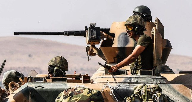 Turkish soldiers sitting in a tank, driving to Syria from the Karkamış district of Turkey's souteastern Gazitantep province on Aug. 27.