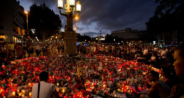 People stand next to candles and flowers placed on the ground, after the terror attack that killed  at least 14 people and wounded over 120 in Barcelona, August 20