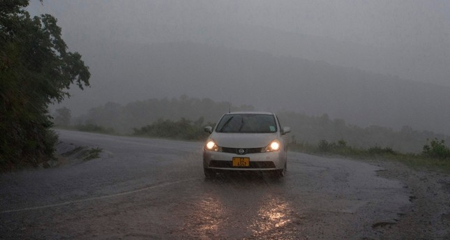 emThis picture taken on March 15, 2019 shows a vehicule as rain, which is believed to be the beginning of Tropical cyclone Idai coming from central Mozambique, falls in the flooded districts of Chikwawaa and Nsanje in southern Malawi (AFP Photo)/em