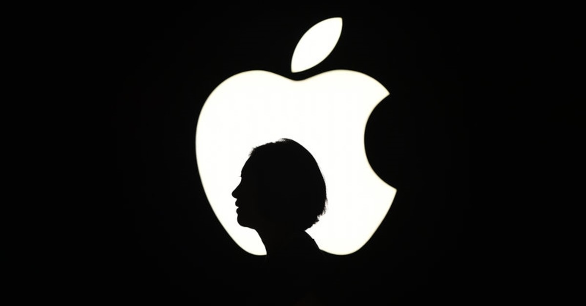 n this file photo taken on September 9, 2015 a reporter walks by an Apple logo during a media event in San Francisco, California. (AFP Photo)
