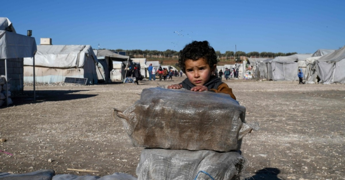 A displaced Syrian boy stands next to bags of aid at a camp for the internally displaced near Dayr Ballut, near the Turkish border in the rebel-held part of Aleppo province on February 9, 2020. (AFP Photo)