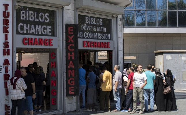 People exchange their money at a currency exchange office in Istanbul, Aug 13.