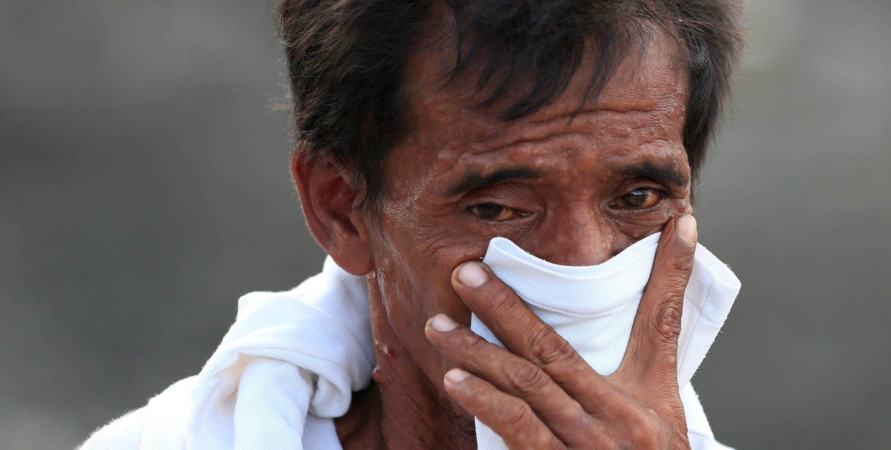 A man covers his nose as rescue members find a dead body from last weeku2019s earthquake, Palu, Oct. 7.