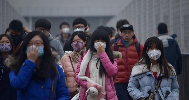 This picture taken on February 24, 2014 shows residents waiting for buses in a bus station in haze-covered Beijing. (AFP Photo)