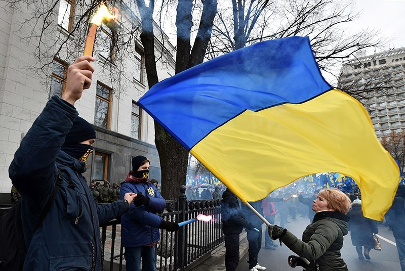 Supporters of various Ukrainian nationalist parties light smoke bombs while a woman waves a Ukrainian national flag in front of them during a rally in front of Ukrainian Parliament, in central Kiev, on Feb. 22, 2017. (AFP Photo)