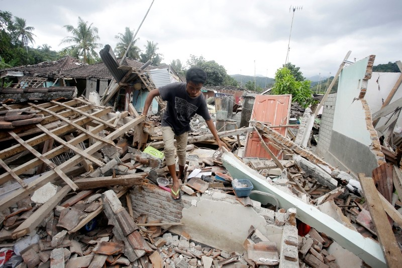 A man walks through debris from Sunday's earthquake in West Lombok, Indonesia, Saturday, Aug. 11, 2018. (AP Photo)