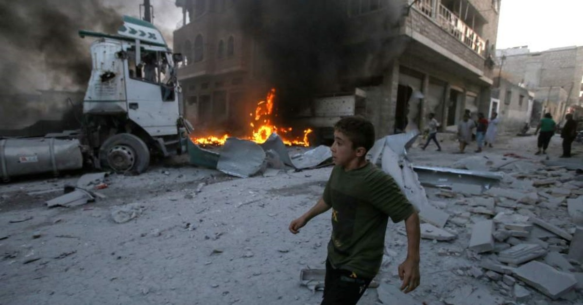 A young boy runs past a fire in a building following a reported airstrike by Syrian regime forces in the town of Maaret al-Numan in Syria's northwestern Idlib province, Aug. 28, 2019.