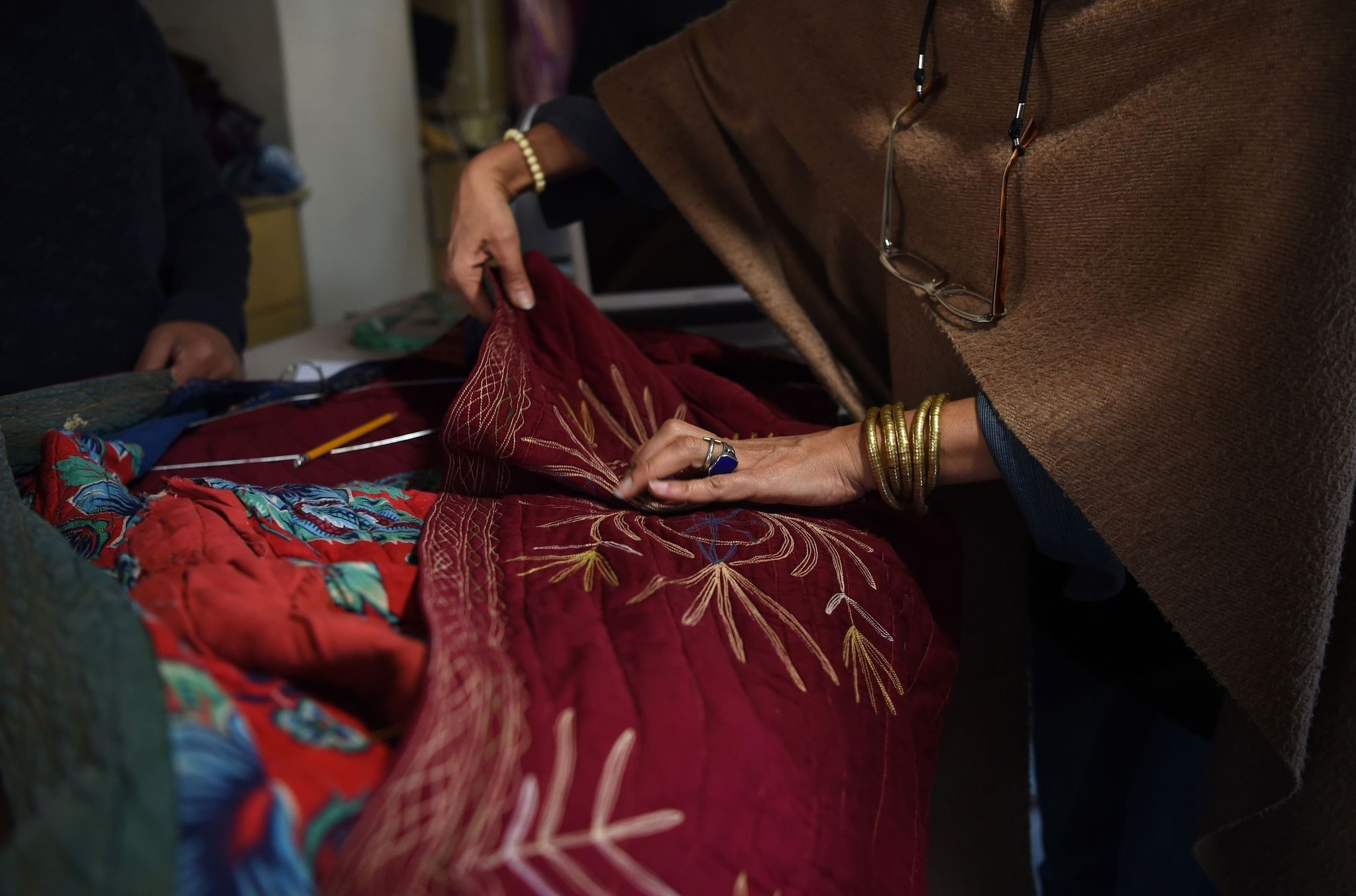 An Afghan tailor works on a cotton fabric piece at Zarif Design House in Kabul.