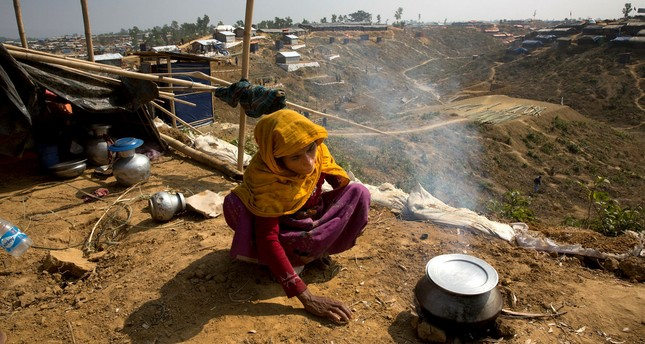 A newly arrived Rohingya woman makes rice for her family at Balukhali refugee camp near Cox's Bazar, Bangladesh, Jan. 13.