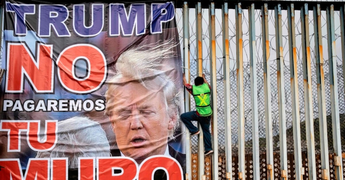 In this file photo taken on February 2, 2020 a member of Border Angels hangs a banner reading ,Trump we will not pay for your wall, during a demo against him at the US-Mexico border in Playas de Tijuana, Baja California state, Mexico.